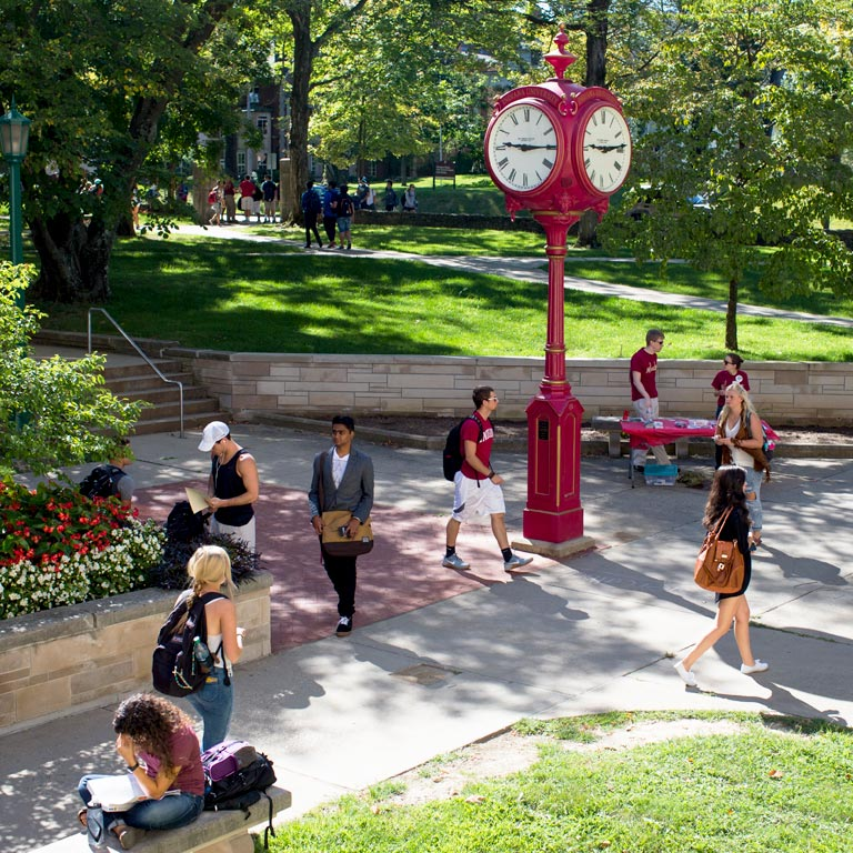 Students walk past a red clock on the IU Bloomington campus.